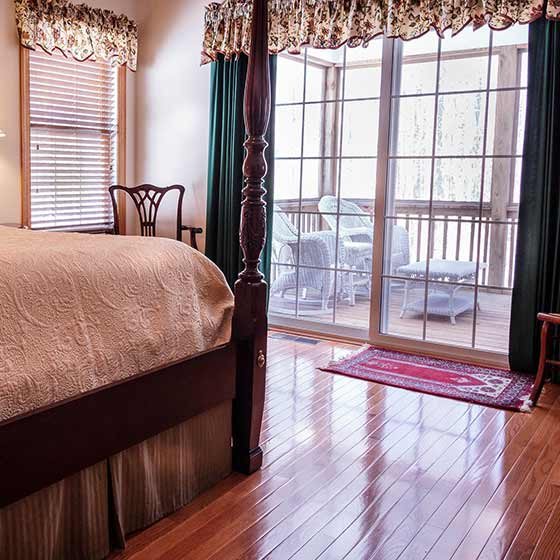Victorian style bedroom with sunlight pouring through the window onto gleaming hardwood floors