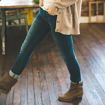 Woman in a beige cardigan, blue jeans, and brown boots stepping on old hardwood floors